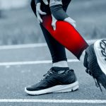 Athletic woman on running track has calf cramp and touching hurt leg